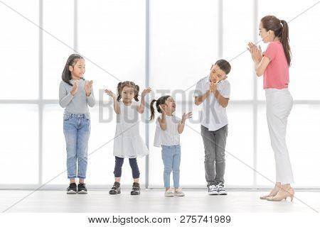 Asian Woman In Pink Shirt Teach Asian Boy And Girls To Playing Something , They Stand In Front Of Bi