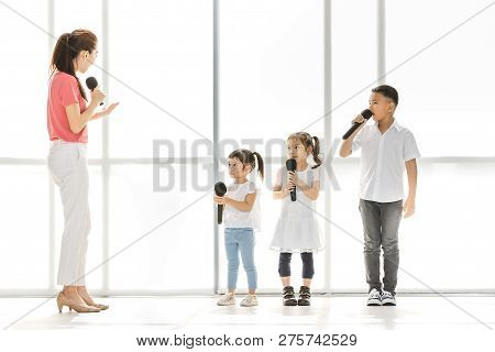 Asian Teacher Teach Asian Kids To Sing A Song, Kids Pay Attention To Listen To Her, They Stand In Fr