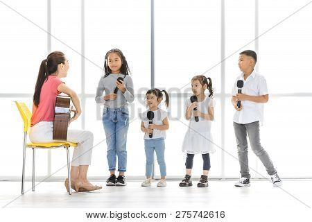 Asian Teacher Sitting On A Chair Play Acoustic Guitar Teach Asian Kids To Sing A Song, Kids Pay Atte