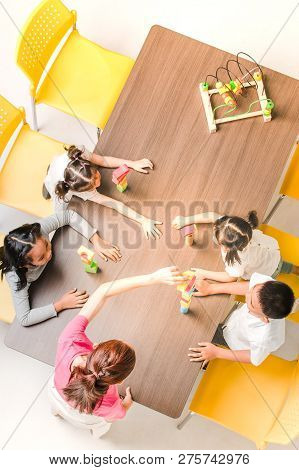 Flat Lay Shot Of Asian Teacher Play Colorful Build Blocks Toy With Asian Student Together, Concept F