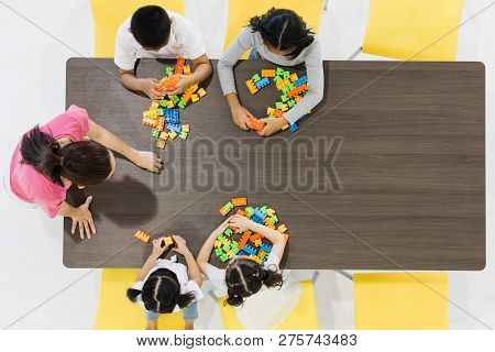 Group Of Kids And Teacher Playing Colorful Toys In Classroom. Concept For Happy And Funny Learning,