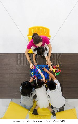Flat Lay Shot Of Asian Teachers Play Colorful Alphabet Puzzle Toy With Asian Students Together, Conc