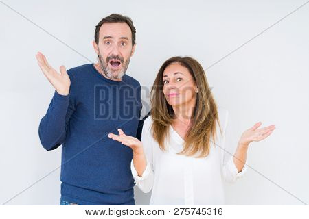 Beautiful middle age couple in love over isolated background clueless and confused expression with arms and hands raised. Doubt concept.