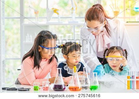 Science Teacher Teach Asian Students In Laboratory Room, Smoke Float Out Of Bowl, They Excited, Colo
