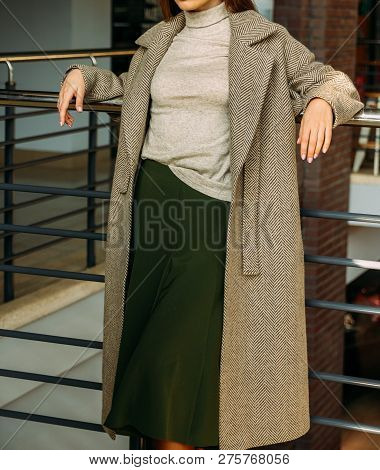 A Girl In A Beige Coat And Sweater, A Green, Long Skirt, Stands Near The Railing, Leaning On The Rai