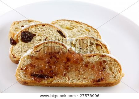 Sweet Jam on a  slice of homemade Christmas stollen cake with raisins, nuts, spices and chopped dried fruit