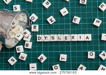 Dyslexia Word Made Of Square Letter Word On Green Square Mat Background.