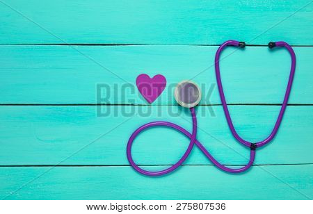 Stethoscope And Heart On A Blue Wooden Table. Cardiology Equipment For Diagnosing Cardiovascular Dis