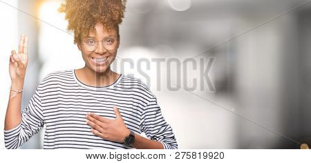 Beautiful young african american woman wearing glasses over isolated background Swearing with hand on chest and fingers, making a loyalty promise oath poster