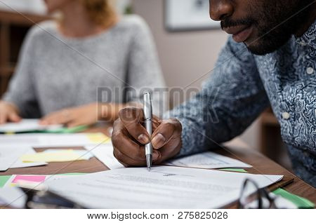 Closeup of businessman hand signing on formal paper during a meeting in boardroom. African american business man signing a contract. Closeup of a businessperson sign contract and making a deal.