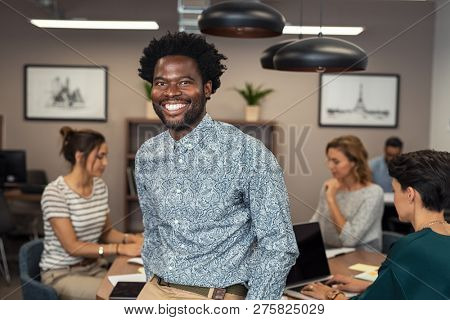 Portrait of happy african businessman looking at camera and sitting at desk. Mature business man in office with colleagues working in background. Successful african american man in casual standing.