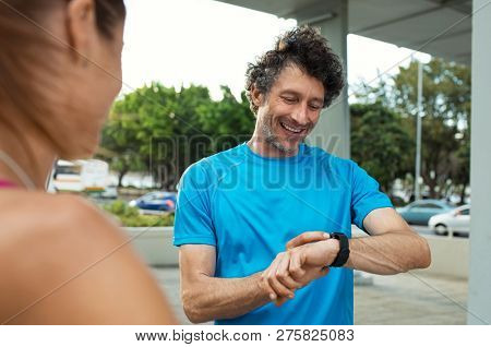 Mature jogger checking time on smart watch during running exercise. Smiling runner looking at smartwatch, checking gps position map. Happy fitness man checking heart rate monitor on wrist.   poster