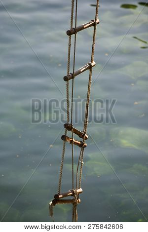 Achieving Success. Rope Ladder. Jacobs Ladder. Rope Ladder With Wooden Steps. Rope Over Water Surfac