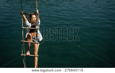 The Highest Ambition. Sensual Woman Hang On Rope Over Water Surface. Pretty Woman Climb Jacobs Ladde