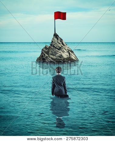 Businessman In The Ocean Walking To A Red Flag. The Concept Of Reaching Goals.