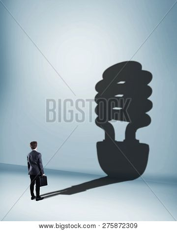 Businessman Standing In Front Of Wall With Light Bulb Shadow.