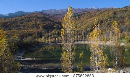 Top View Of Lake With Autumn Forest And Mountains. Shot. Drying Up Mountain Lake In Autumn. Pictures