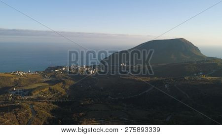 Top View Of Panorama Of Coastal Town. Shot. Town Is Located At Foothills On Beach Sea. Small Industr