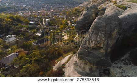 Top View Of Stone Cliffs Hanging On Town. Shot. Houses Located In Valley Surrounded By Hills With Ro