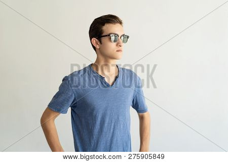 Serious Cool Guy In Sunglasses Wearing Blue Tshirt And Looking Into Distance. Handsome Man Planning