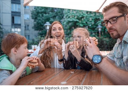 happy family sitting at a table in a fast food restaurant