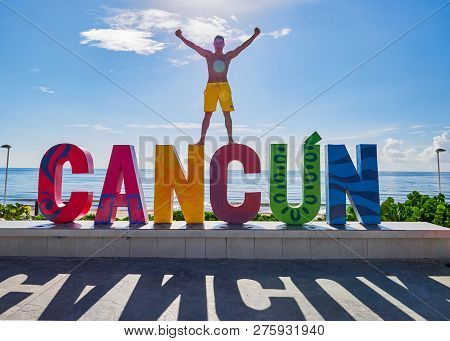 Boy Celebrates With Raised Arms On Cancun Sign, Playa Delfines, Cancun, September 7, 2018.