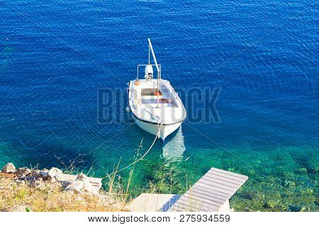 A Small White Fishing Boat Tied At The Pier. White Boat In The Blue Clear Sea, Picturesque Photo. Th
