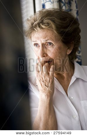 Sad elderly woman looking out window