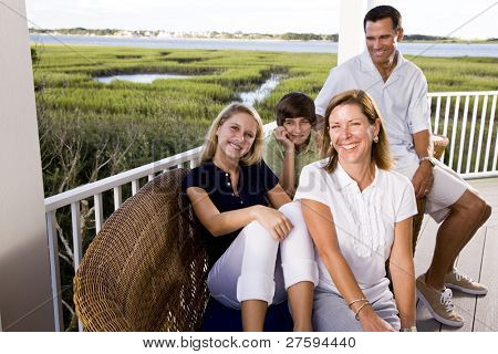 Family with teenager children on vacation sitting together on terrace