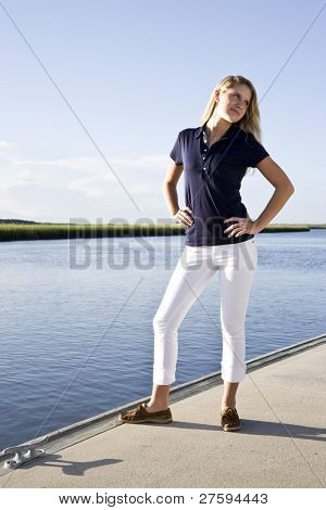 Teenage girl standing posed on dock by water on sunny day