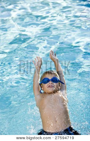 Happy boy wearing swim goggles, swimming on his back in pool, 7 years.