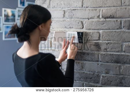 Young Woman Entering Security Pin On Home Alarm Keypad.