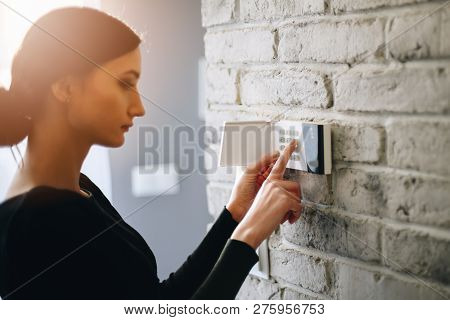 Woman Entering Security Pin On Home Alarm Keypad.