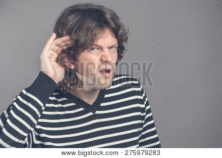 Unhappy Hard Of Hearing Man Placing Hand On Ear Asking Someone To Speak Up Or Listening To Bad News