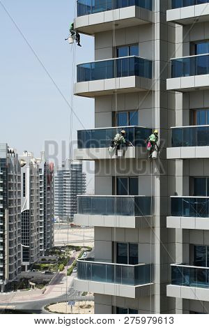 High-rise Workers Wearing Seat Belts Wash The Windows Of A High-rise Building In Dubai