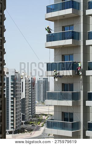 Three High-rise Workers Wash Windows Of A High-rise Building In Dubai