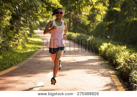 Female Runner Running At Summer Park Trail . Healthy Fitness Woman Jogging Outdoors.