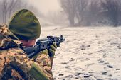 A military soldier with a Kalashnikov assault rifle conducts aimed fire at the enemy in winter, dressed in camouflage to prevent the enemy from advancing. poster