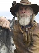 Rugged authentic cowboy with his horse wearing traditional clothing. poster