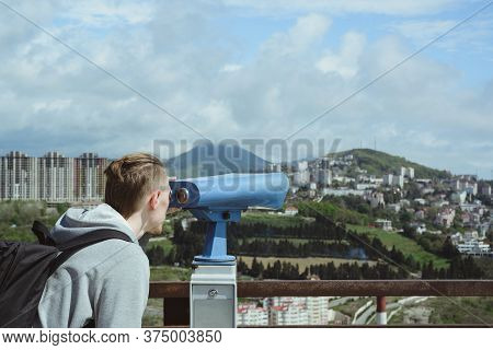Young Caucasian Hipster Man Looking Through Stationary Binoculars At Sea, Mountains And City On Obse