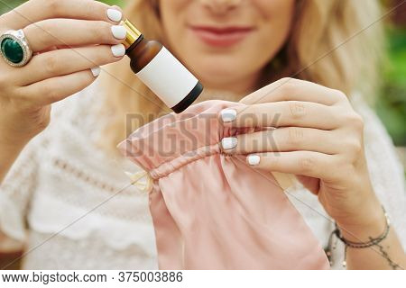 Close-up Image Of Smiling Young Woman Taking Bottle Of Revitalizing Brightening Serum Out Of Light P