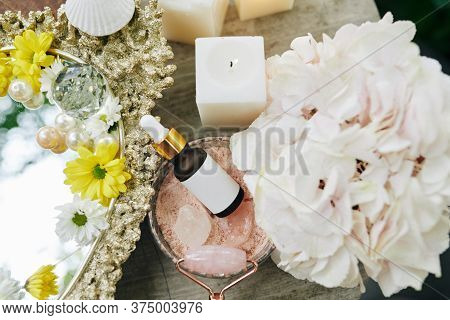 Small Bottle Of Brightening Serum For Face Massage With Quartz Roller On Table With Flowers And Burn