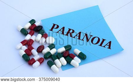 Paranoia Words On A Blue Sheet Of Paper Against The Background Of Multicolored Tablets. Medical Conc