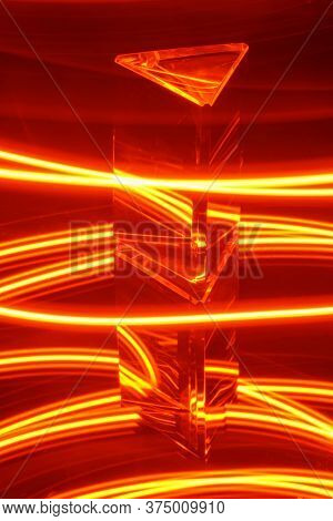 Glass Prism With Reflection On A Abstract Red And Yellow Neon Light Stripey Background
