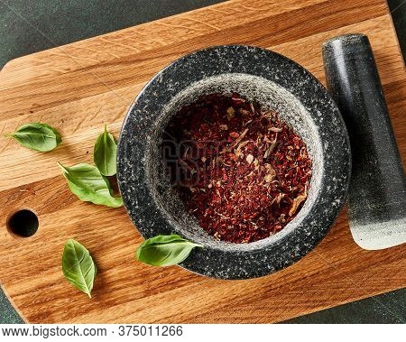 Top View Of In A Marble Mortar. Red Pepper, And Basil Leaves On Wooden Board.