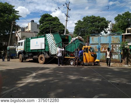 Closeup Of Garbage Collecting Workers Working To Unload Waste From Auto To Lorry In A Roadside.