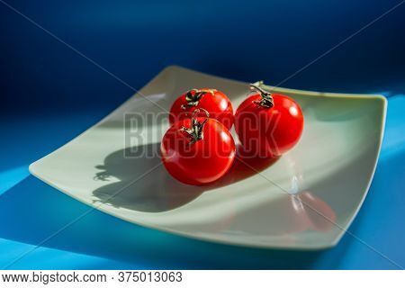Three Red Tomatoes Lie On A Plate In The Sunlight. Summer Season.