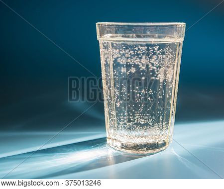 Glass Of Water Stands On A Table Lit By Sunlight. Summer Season.