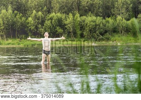 A Young Man Stands In The River And With Outstretched Arms Enjoys Nature.