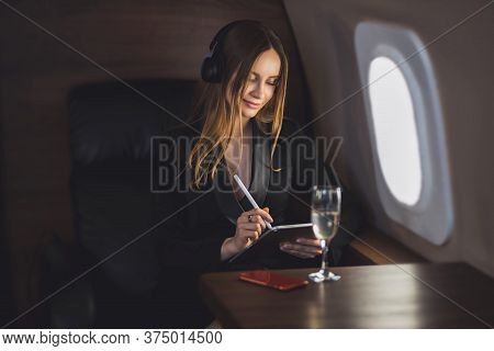 Attractive Businesswoman Using Digital Tablet In Private Plane. Lovely Caucasian Young Woman In Styl
